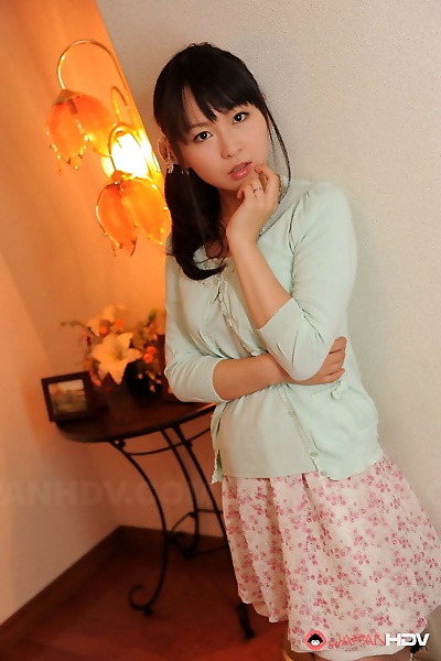Fully clothed Japanese girl Nozomi Hazuki holds her face firm in printed skirt
